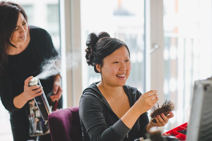 Die Haare asiatischer Braut werden beim Getting Ready durch Visagistin mit Spray besprüht
