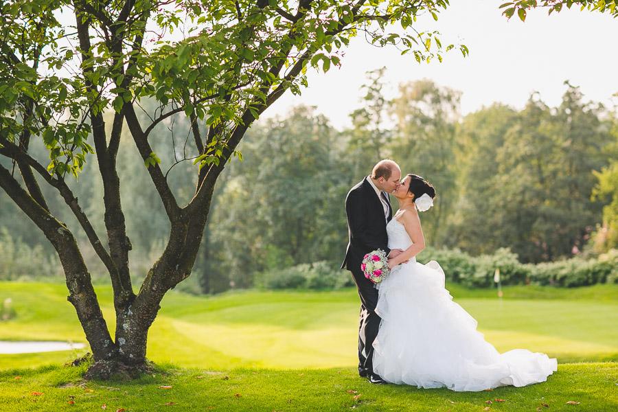 Brautpaar küsst sich auf Golfrasen von der Hochzeitslocation Kosaido in Düsseldorf erstrahlt vom stimmungsvollen Licht