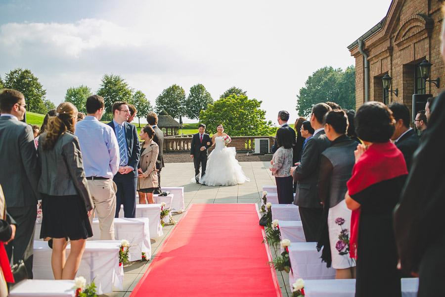 Bei der freien Trauung auf der Terrasse vom Kosaido in Düsseldorf wird die Braut von ihrem Vater über einen roten Teppich zum Bräutigam geführt