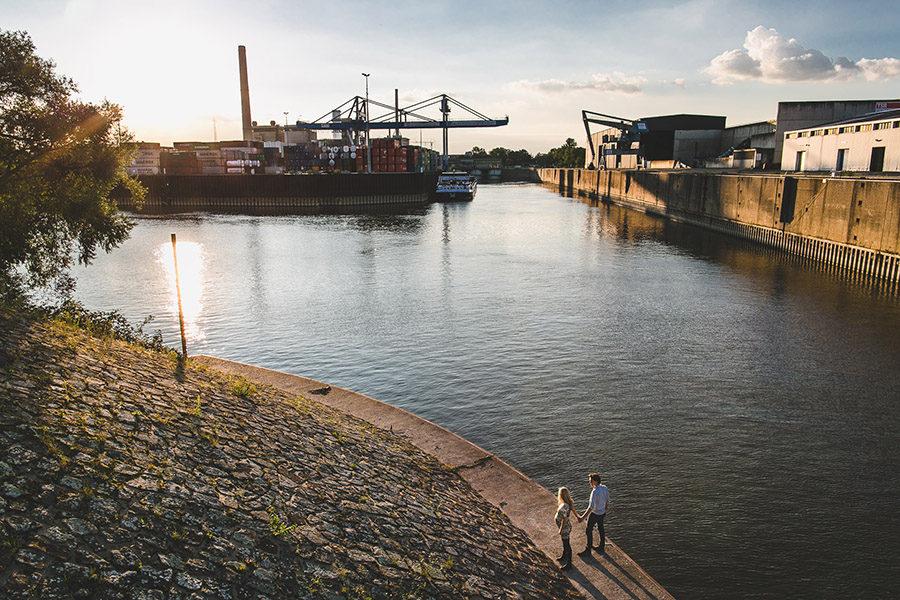 Pärchen mit schwangeren Frau hält Händchen. Im Hintergrund der Industrie Hafen in Düsseldorf beim Sonnenuntergang. Perspektive von oben.