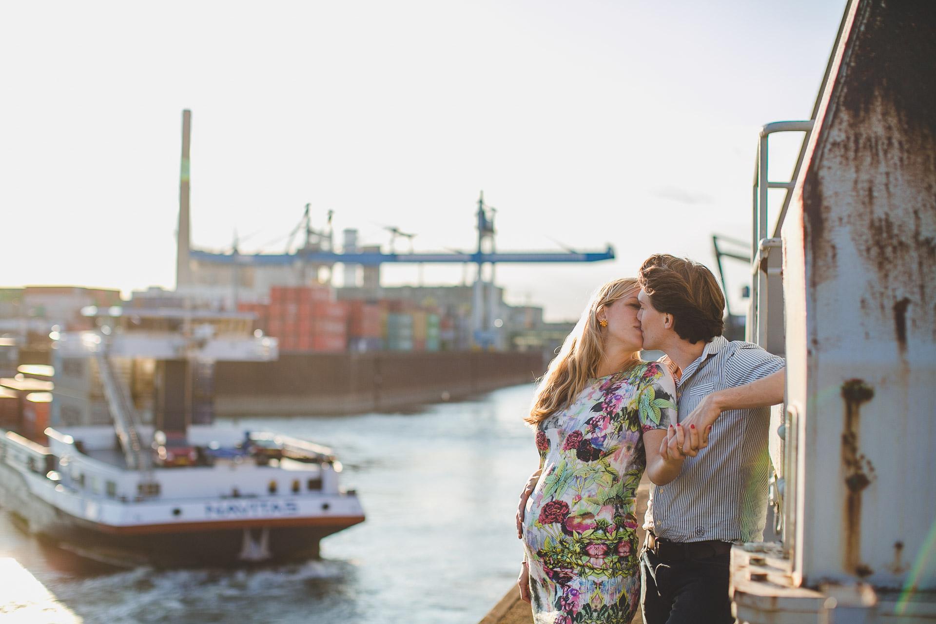Schwangere mit Babybauch küsst ihren Partner am Industrie Hafen in Düsseldorf. Ein Schiff nähr sich. Industrie Kulissen.