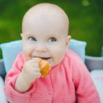 Süßes Baby sitzt im Babystuhl, hält ein Brötchen und schaut sehr putzig nach oben