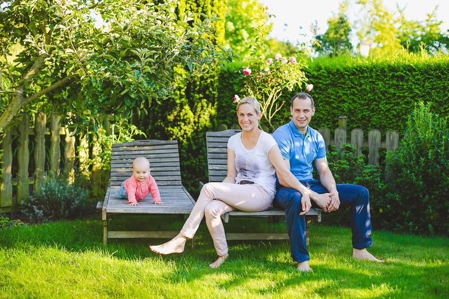 Baby mit seinen Eltern im gepflegten Garten auf Holzliegen.