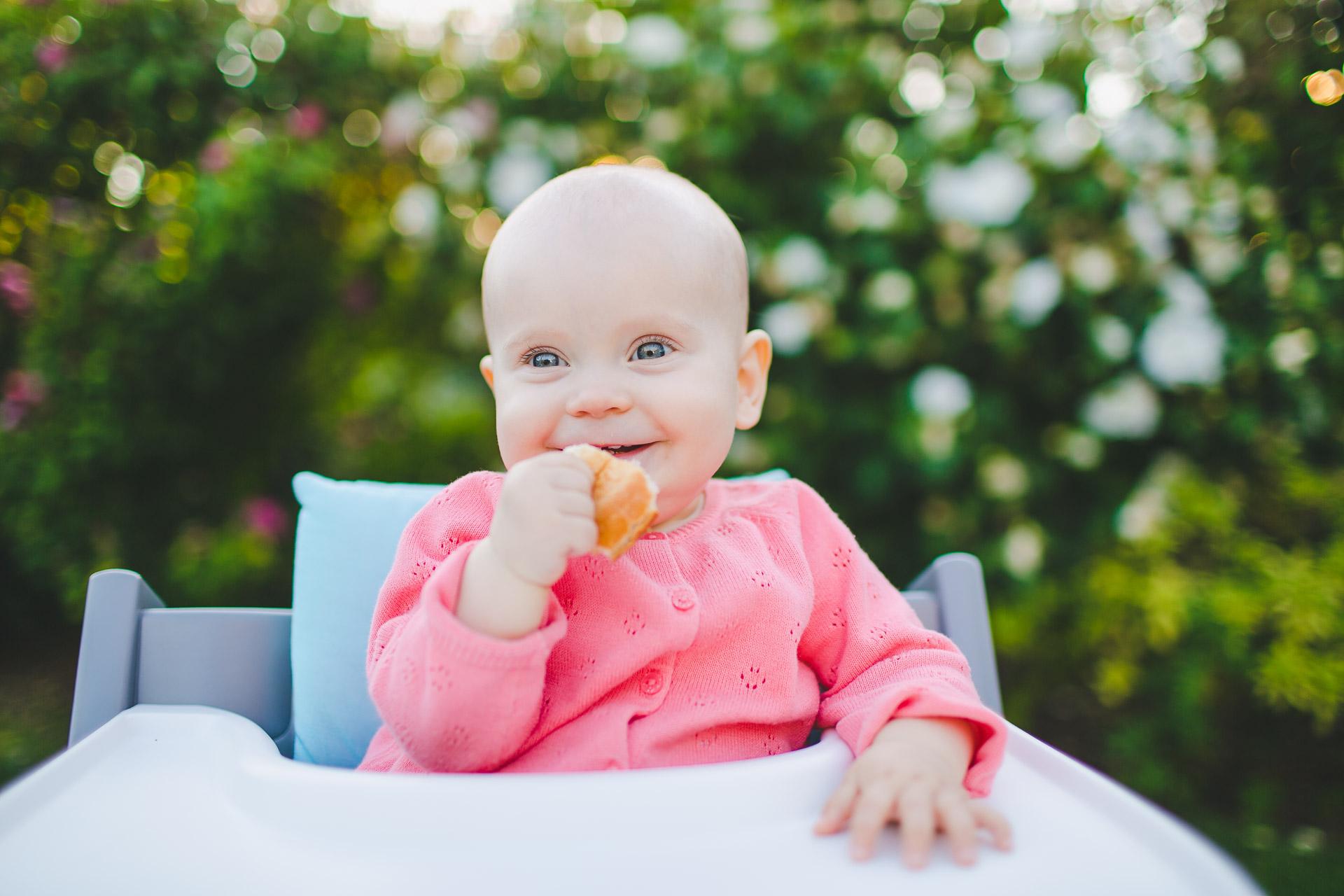 Zuckersüßes Baby im Garten mit Brötchen lächelt in der Hand