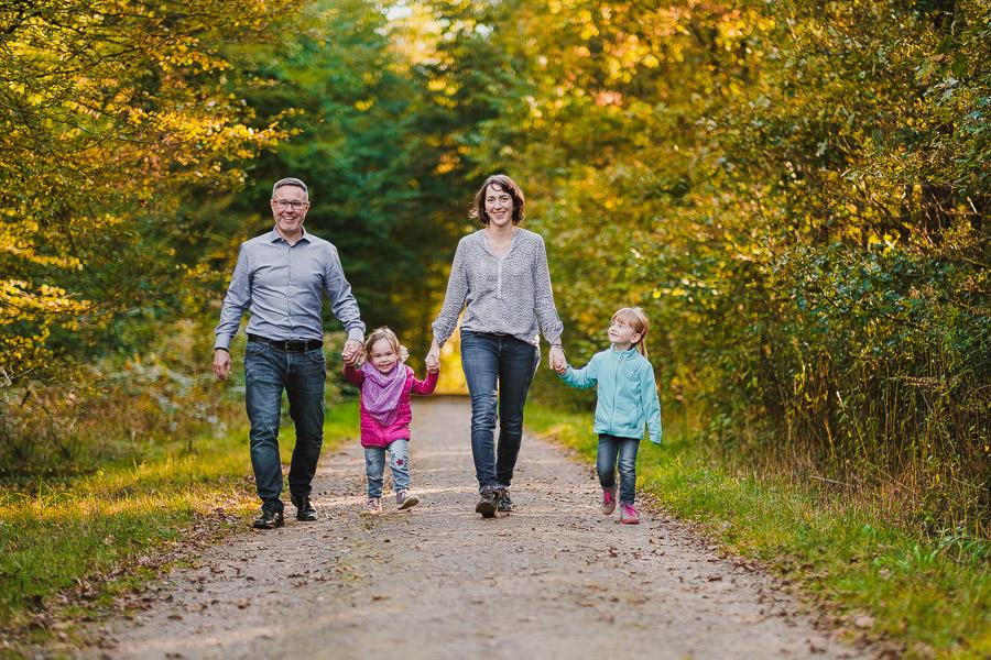 Eltern gehen Hand in Hand mit zwei Kindern auf Waldweg im Herbst.