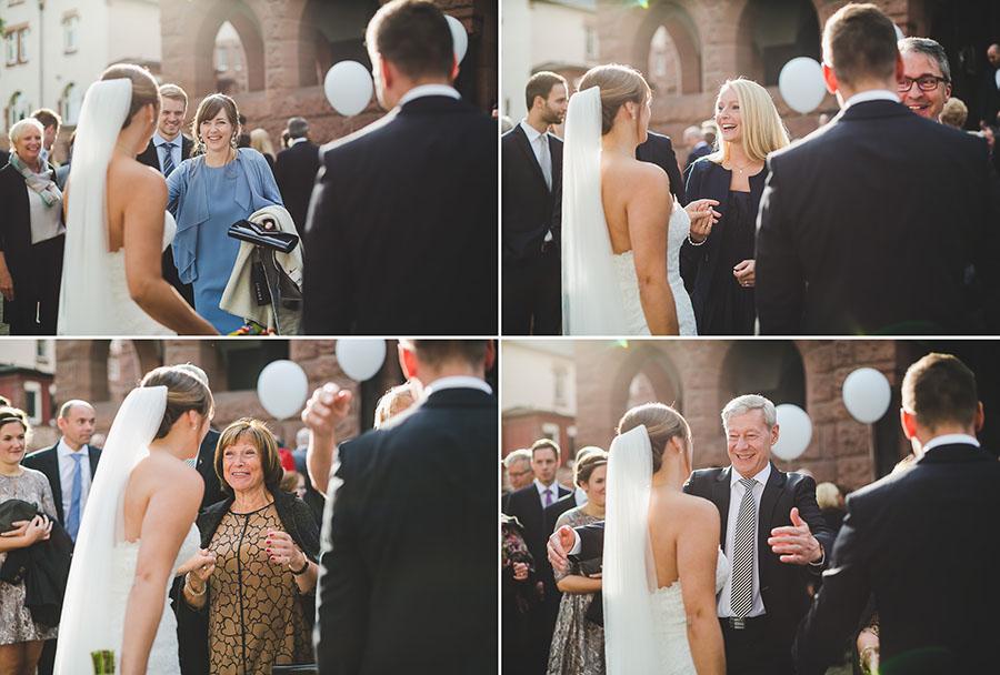 Hochzeitsgäste gratulieren dem Brautpaar vor Kirche St. Nikolaus in Essen. Viel Gegenlicht.