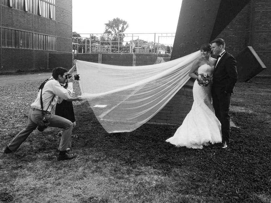 Hochzeitsfotograf Vladimir Dimitrov macht Bilder vom Brautpaar. Mädchen hält den Schleier für eine interessante Perspektive.