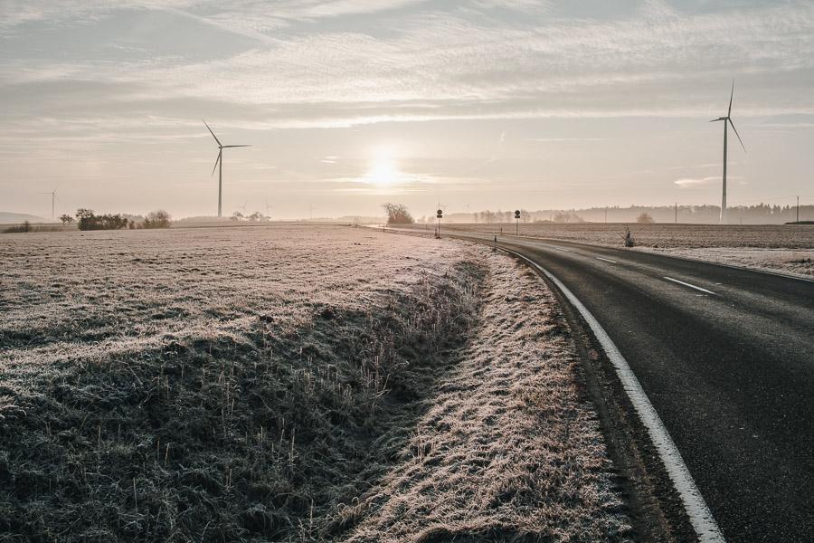 Landschaft im Winter mit Straße und Windgenerator