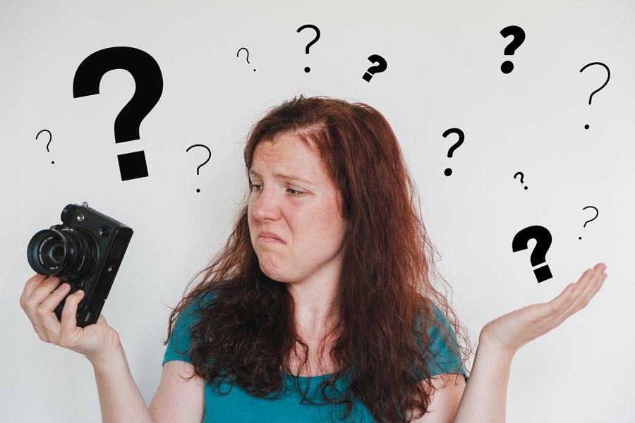 Frau mit Kamera und Fragezeichen