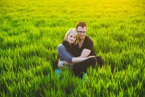 romantisches Paar umarmt sich im Feld bei Sonnenuntergang im Rahmen vom Engagement-Shooting
