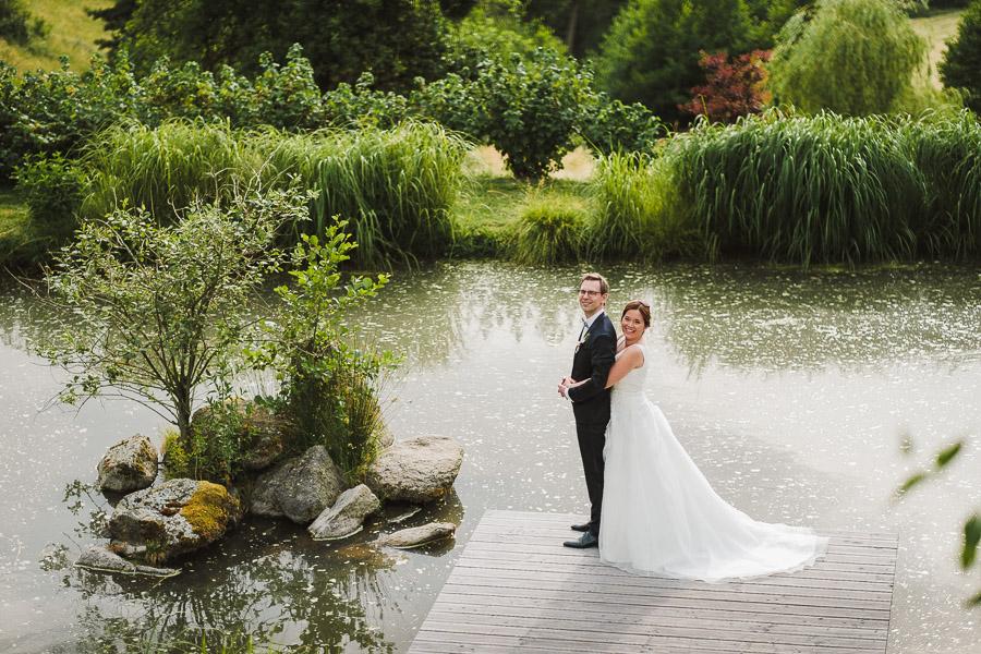 Brautpaar steht auf einem Steg und schaut in die Kamera
