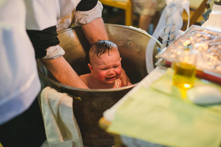 Kind wird weinend im Taufbecken getauft