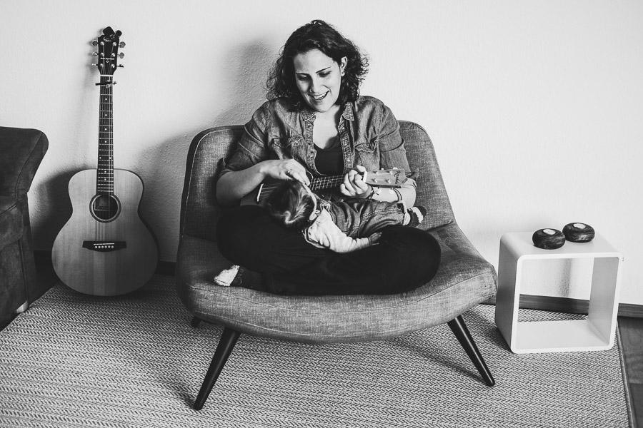 mutter spielt ihrem baby okulele gitarre im hintergrund