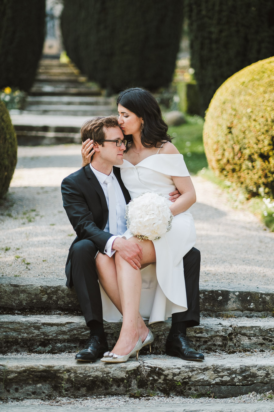 braut sitzt auf dem schoss von bräutigam beim hochzeitsshooting in kronberg