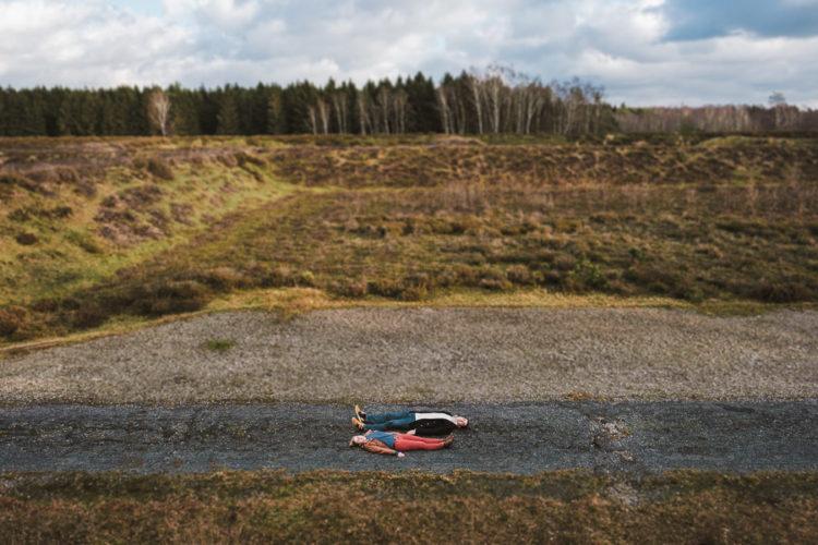 Bild eines Pärchen von oben liegend auf dem Rücken im Wald