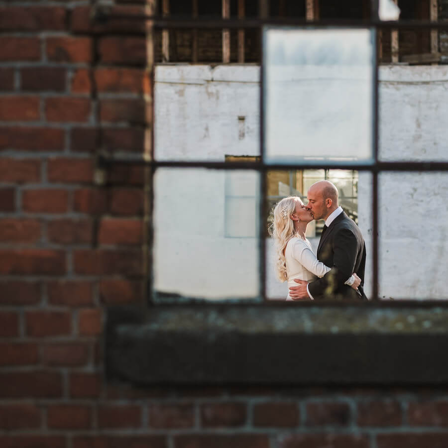 hochzeitspaar kreativ durch kaputtes fenster alte fabrik fotografiert