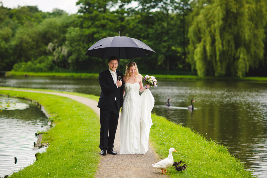 brautpaar macht hochzeitsbilder bei regen draussen